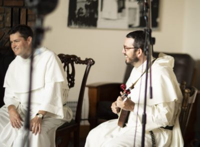 Two Dominicans sit in chairs, smiling, one holding a mandolin, the view partially obscured by microphone stands