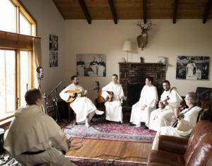 Six Dominicans with instruments sit in a room with a brick fireplace, wood ceiling and musical instruments and recording equipment. Light shines through a large wooded window on the left.